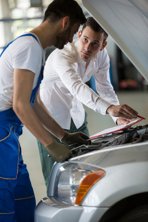 to examine: manager and mechanic examine a car damage Stock Photo