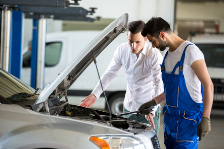 mechanic discussing with customer in garage