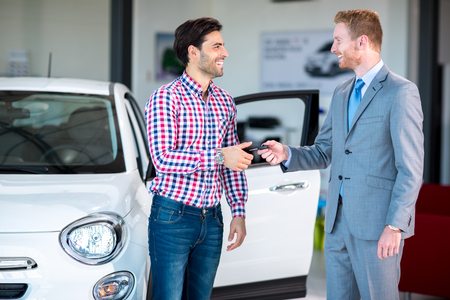 car dealership: Sales situation in a car dealership, the dealer giving key of car at young male,