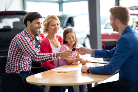 happy customer: car dealer selling new car to young family with child girl