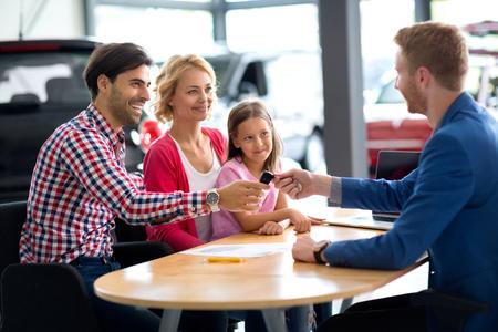 Concesionario de automóviles a vender coches nuevos a la familia joven con la muchacha del niño Foto de archivo - 47504030