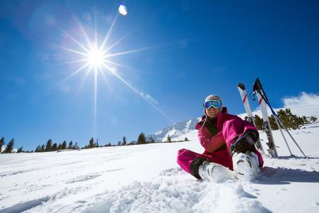 Ski, snow and sun - resting female skier in winter resort