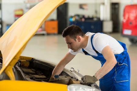 engine bonnet: mechanic working on engine on car