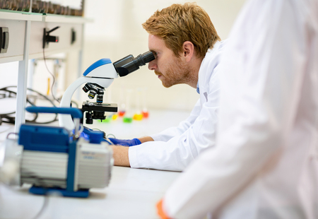 looking into: Young Caucasian scientist looking into microscope