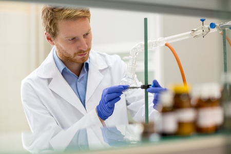 bata de laboratorio: Joven asistente de laboratorio preparar instrumento de experimento qu�mico en el laboratorio Foto de archivo