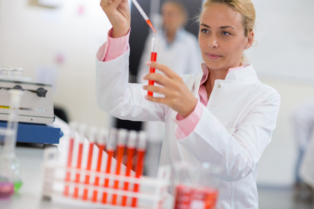 Young chemist sampling liquid with pipette in lab