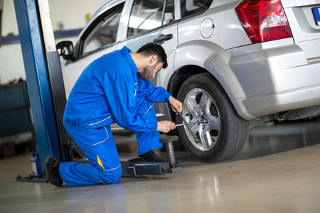 Mechanic change tyre on car Archivio Fotografico