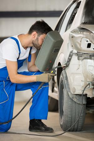 mechanic welding car body in service Stock Photo