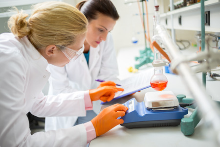 lab coat: Female technicians adjusting measuring instrument in laboratory