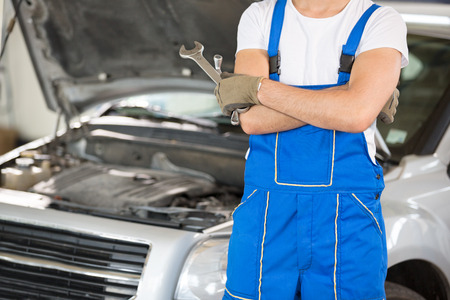 engine bonnet: Mechanic with the tools next to an open hood Stock Photo