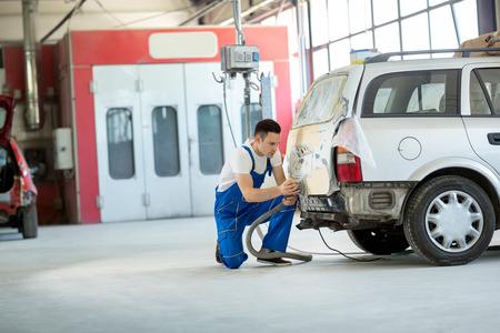 Car painter prepare body part for paint Stock Photo