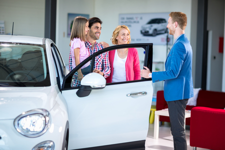 car showroom: Cheerful family in car showroom in car showroom