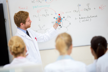 professors: Young male chemistry teacher show molecular model to students in classroom Stock Photo