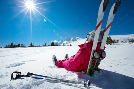 rest and relaxation: Skier relaxing at sunny day on winter season with blue sky in background