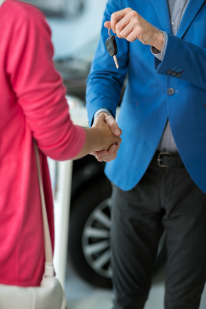 close up of dealer giving key to new owner and shaking hands in auto show or salon