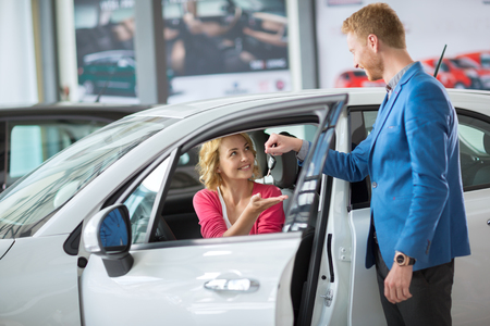 sales manager: smiling woman receives the keys to a new car from a sales manager