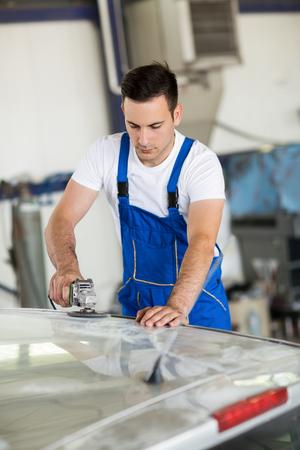 Car painter polishing part on car