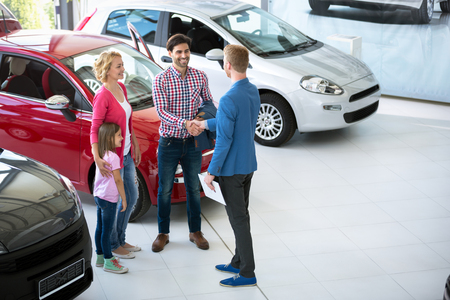 automobile dealership: car salesman showing new vehicle to family customers