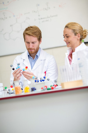 molecular model: Professor and his assistant studying molecular model in chemical cabinet
