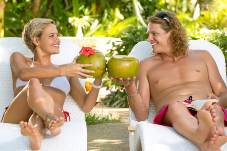 summer fruits: Attractive couple toasting with coconut, exotic vacations Stock Photo