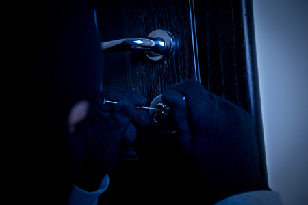 lock and key: masked burglar with a lock-picking tools