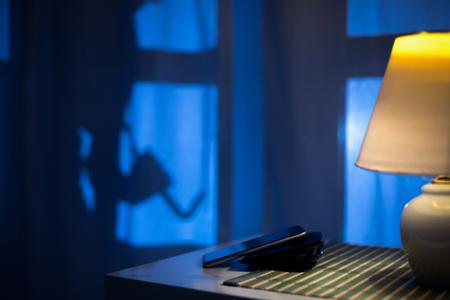 schaduw van een inbreker of een dief sluipen om backdoor 's nachts, te bekijken vanuit de residentie.