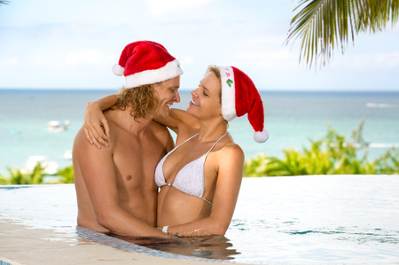 tropical christmas: Romantic couple hugging in swimming pool, enjoying in tropical Christmas vacations