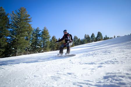 snowboarding: Sportsman snowboarding on the slope Stock Photo
