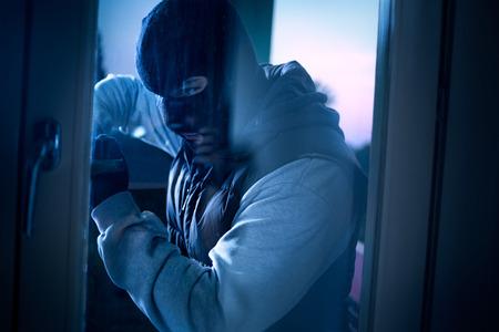 ladron: Ladrón con la palanca para romper la puerta para entrar en la casa