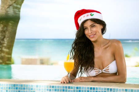 christmas hat: beauty woman with Christmas hat in swimming pool drinking cocktail