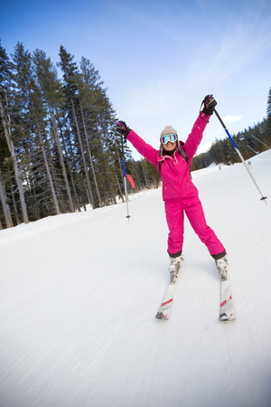 bulgaria: Young happy woman skier with hands up on slope