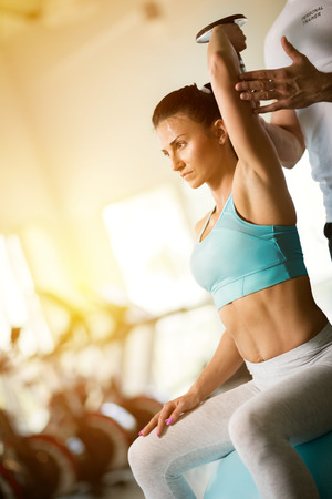Woman doing  lifting dumbbells exercises with personal trainer