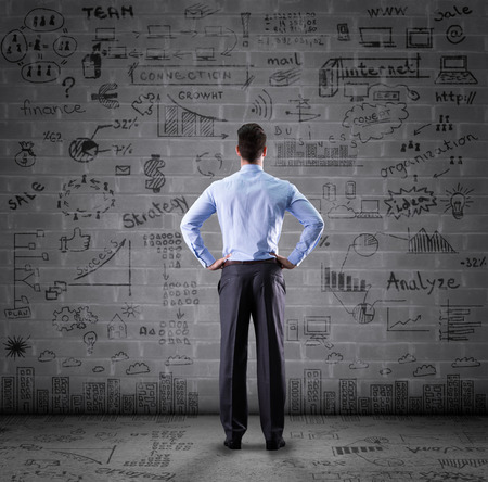 business concept, thinking man looking at drawing wall Stock Photo