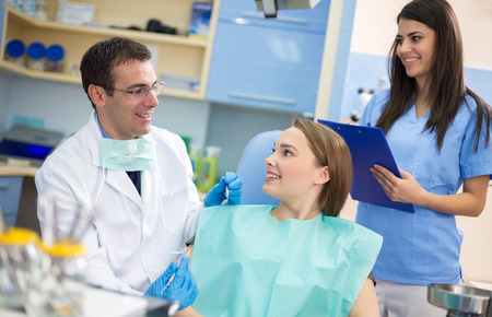 Dentist with smiling assistant and young client satisfied after repairing tooth