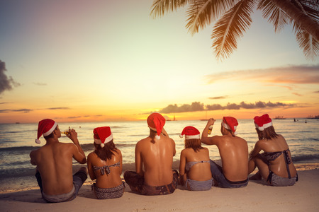 christmas hats: group of friends in Santa helper hats on beach, back view