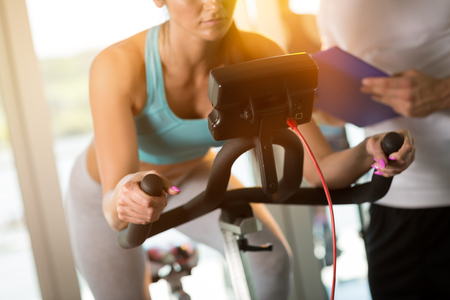 'personal beauty': Woman on exercise bike with trainer at gym Stock Photo