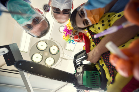scary clown: Scary clown with chainsaw from horror with dental team in bottom view