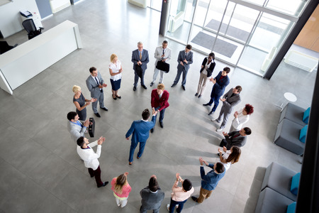 work group: Top view of business arrangement and shaking hands of businessmen in center of circle Stock Photo