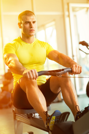 vertical wellness: Young man in health club exercise on row machine Stock Photo