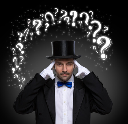 conjuror: thinking magician surrounded by question marks