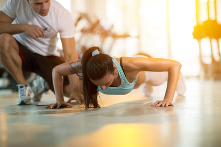 fitness trainer: Gym woman doing push ups with assisting her personal trainer