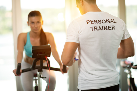 Personal trainer at the gym with client on bike Stock Photo