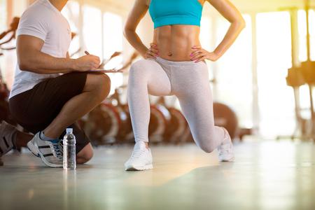 フィットネス ジムでトレーナーとスポーティな女性の運動します。