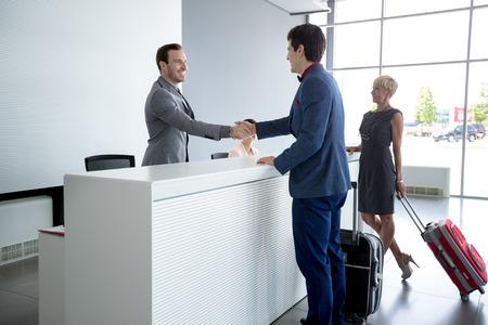 Man and receptionist handshake at reception hall