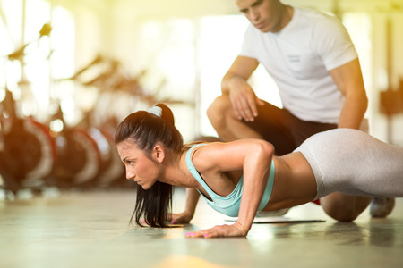sunlight: Personal trainer working with his client in gym