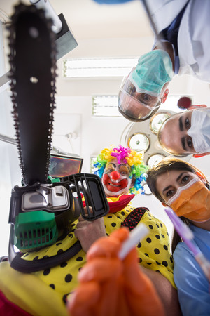 operating table: Dental nightmare with crazy clown with chainsaw on  operating table in bottom view