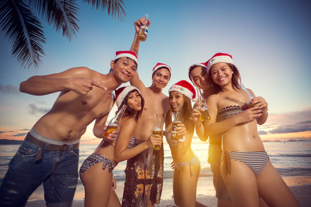 Young happy people on beach having Christmas party, vacation Christmas Stock Photo