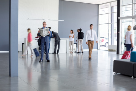areas: Man in elegant male clothes read  newspaper on airport