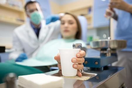 Close up of girl in dental chair take glass of water Stock Photo
