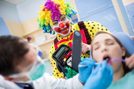 ambulant: Crazy colorful clown with chainsaw in dental ambulant